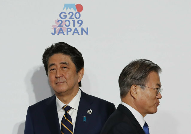 South Korean President Moon Jae-in, right, is welcomed by Japanese Prime Minister Shinzo Abe upon his arrival for a welcome and family photo session at G-20 leaders summit in Osaka, western Japan, Friday, June 28, 2019.