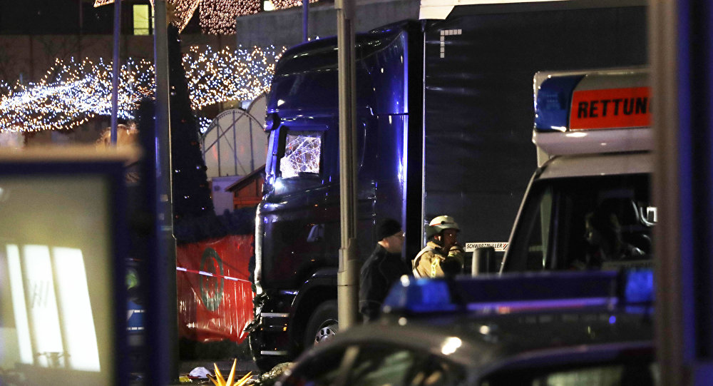 Police stand beside a damaged truck which ran into crowded Christmas market in Berlin, Germany.