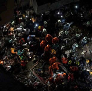 Rescue workers search for survivors at the site of a collapsed building in Mumbai, India, July 16, 2019