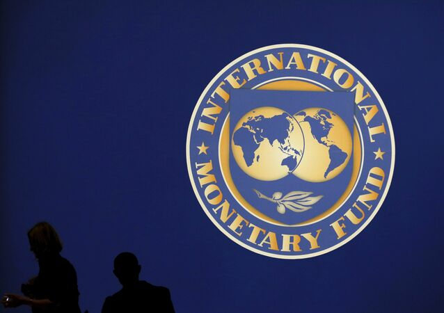 Visitors are silhouetted against the logo of the International Monetary Fund at the main venue for the IMF and World Bank annual meeting in Tokyo in this October 10, 2012 file photo.