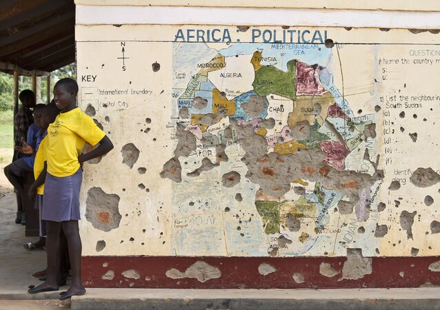 Students line up outside a classroom with a map of Africa on its wall